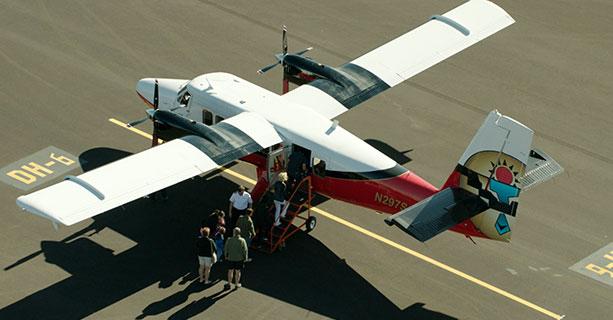 Passengers board a Twin Otter aircraft.