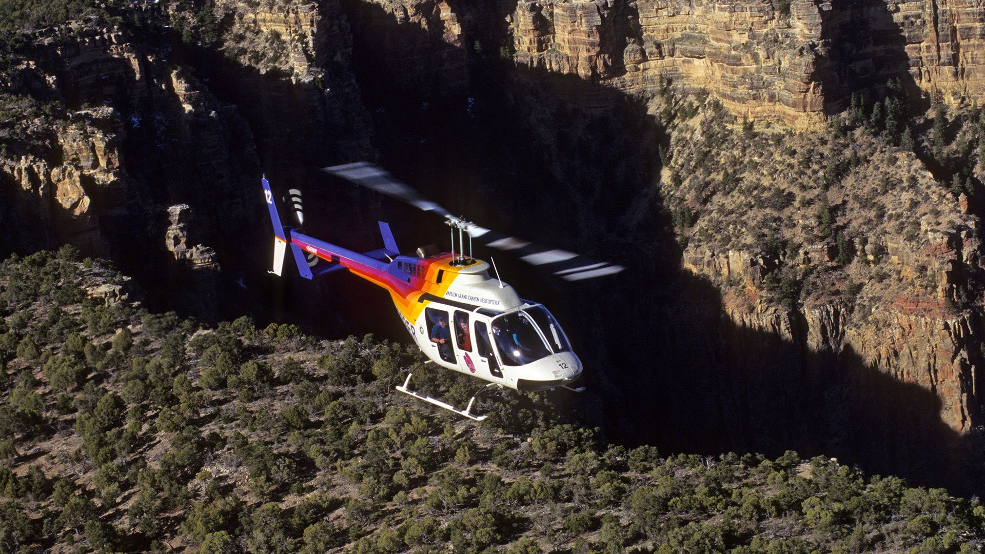 Bell helicopter flying over the Grand Canyon South Rim.