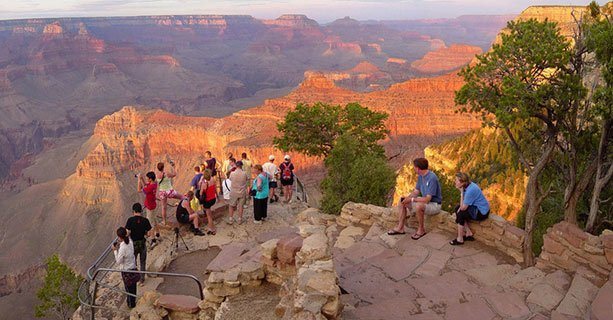 Sightseers stand at the edge of a Grand Canyon viewpoint.