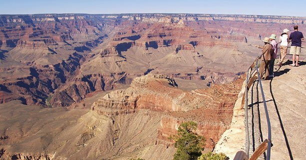 A group of sightseers stand at the edge of the Grand Canyon.
