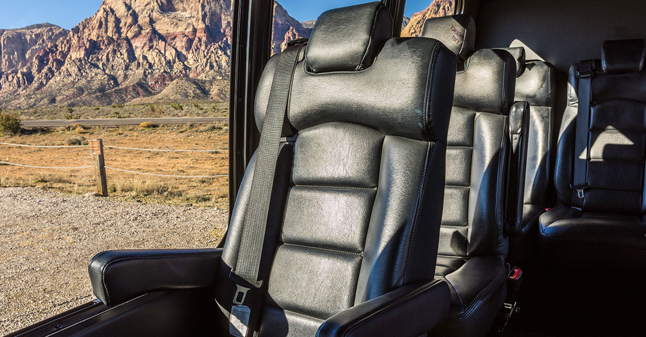 Seating within a cabin of a touring vehicle with the desert visible through large windows.'