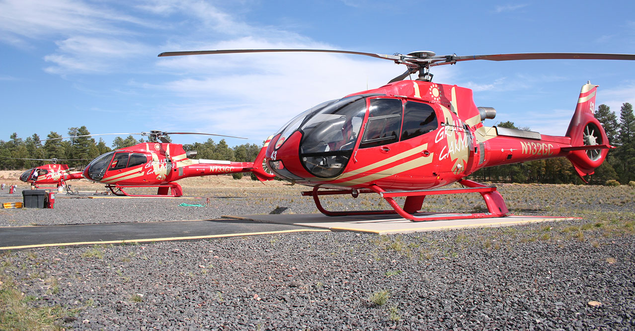 Three red helicopters parked in front of a forested backdrop.