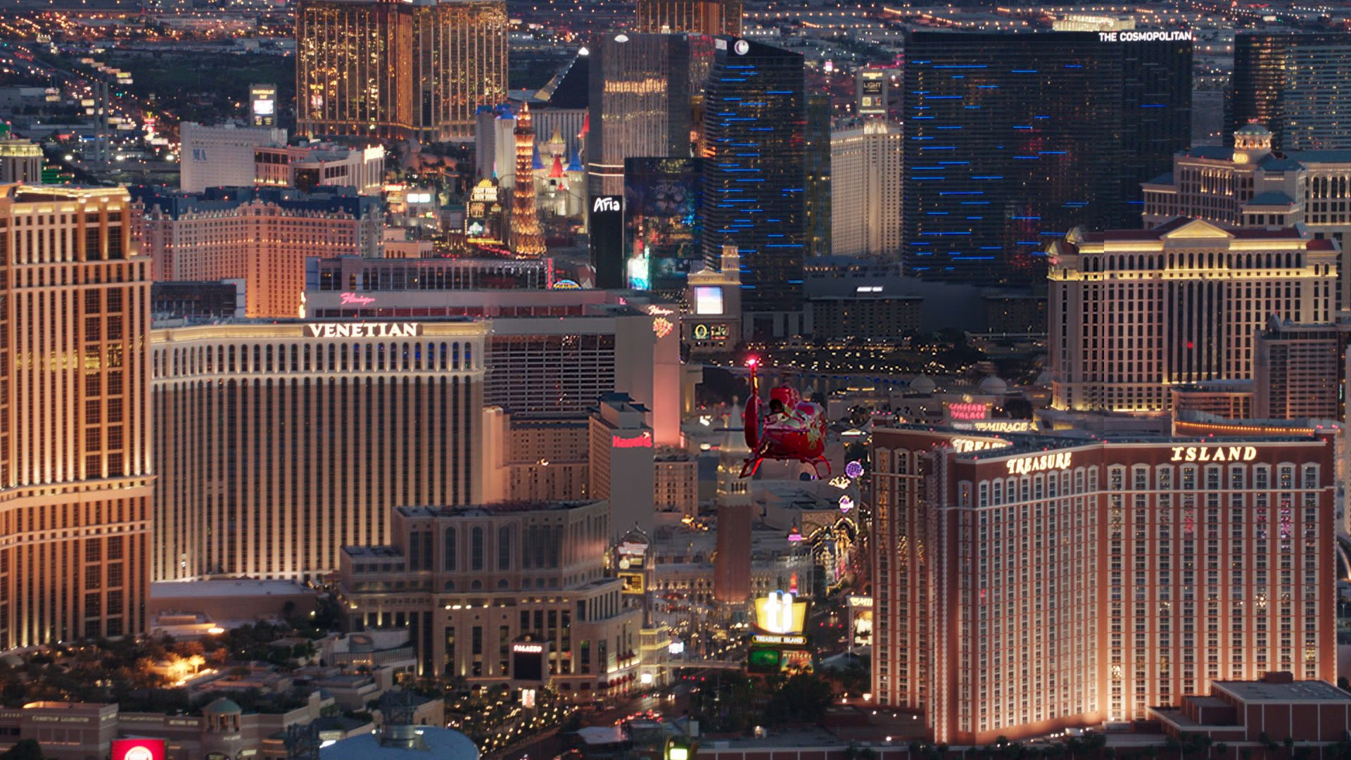 An EC-130 helicopter flies over the Las Vegas Strip at night.