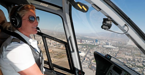 A pilot navigating a Las Vegas helicopter tour with the Strip casinos in the background.