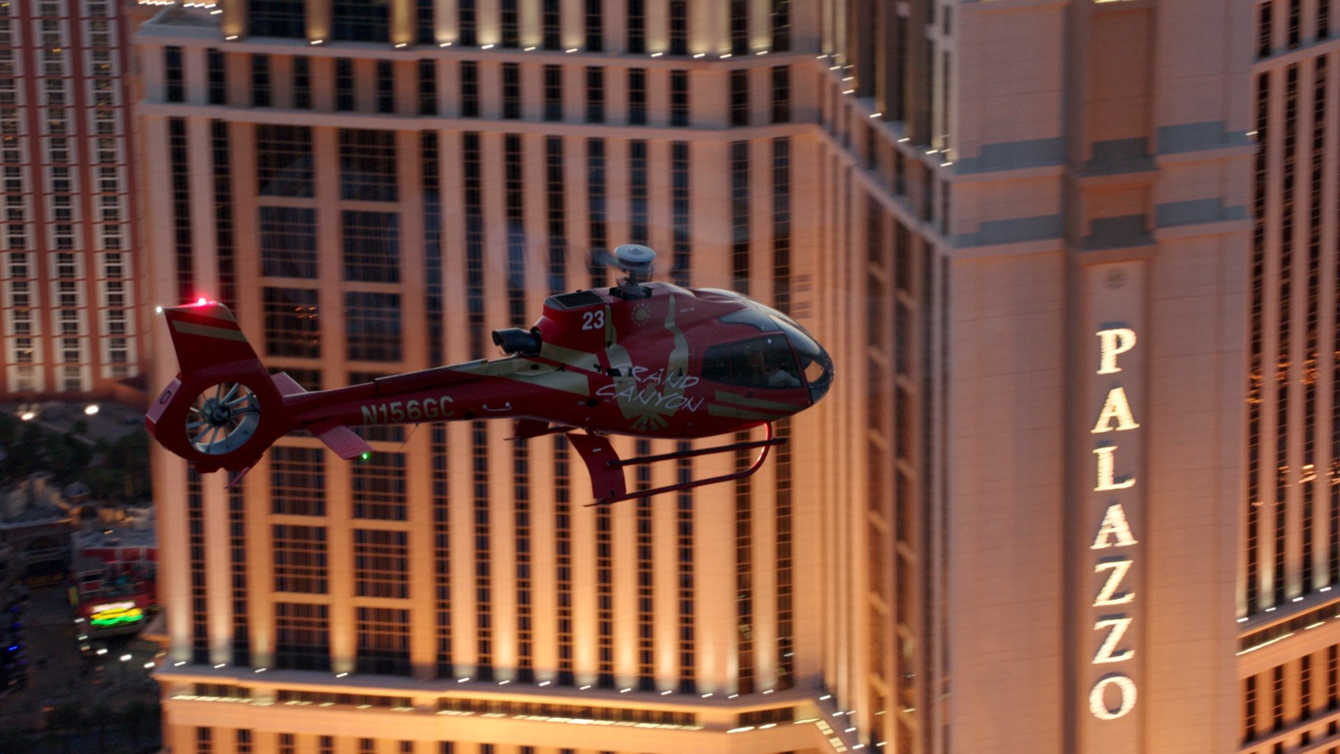 An EC-130 helicopter flying over the Las Vegas Strip with the Palazzo hotel in the background.