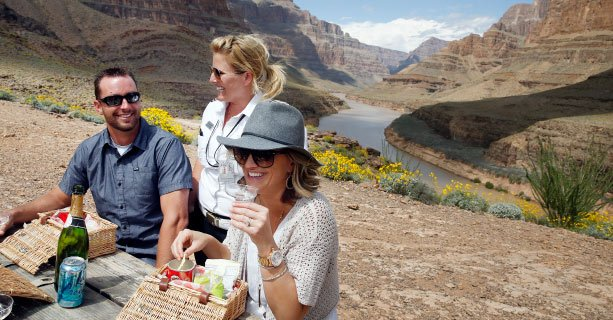 A couple enjoys a champagne picnic on the floor of the Grand Canyon.