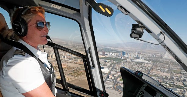 A female pilot navigates a helicopter over the city of Las Vegas.