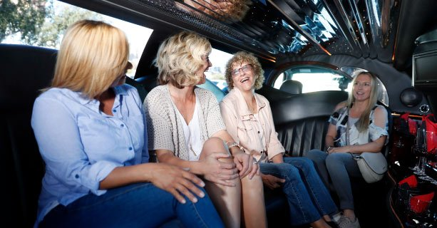 A group of women laugh together inside a limousine.