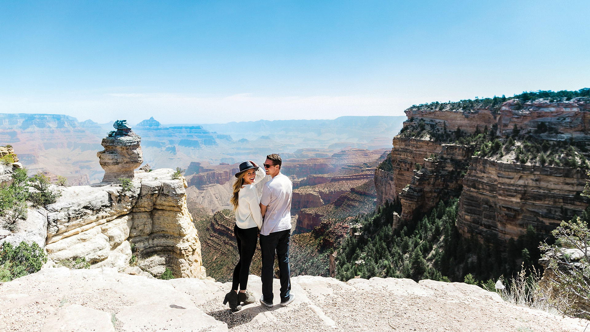 A couple poses at the edge of a Grand Canyon lookout point.