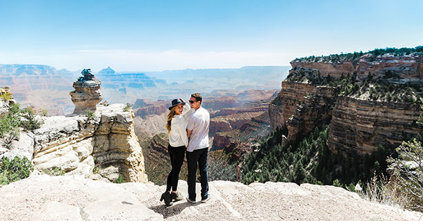 A couple poses together at the edge of the Grand Canyon.