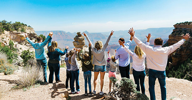 A family poses excitedly at a Grand Canyon viewpoint.