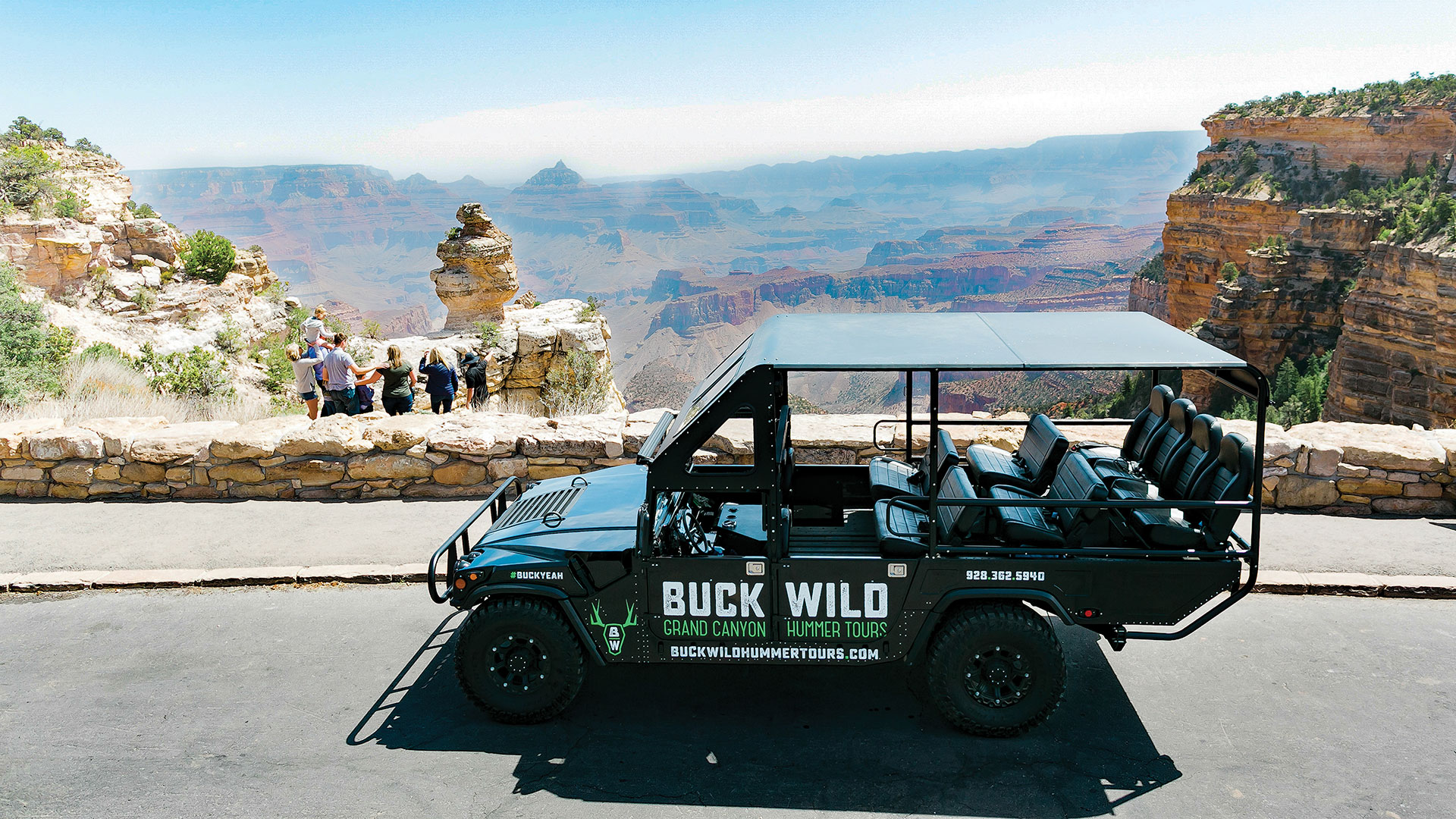 Family facing a Grand Canyon overlook with custom touring Hummer in foreground.