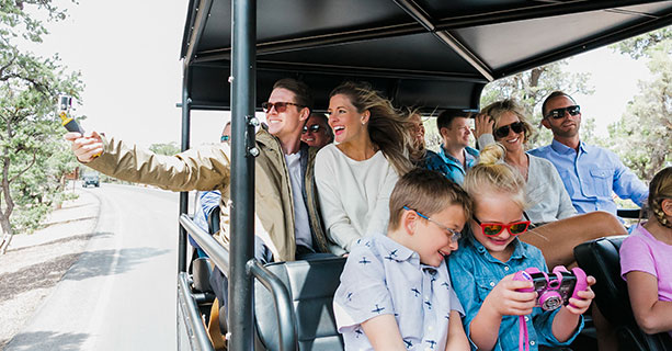 Excited passengers take photos aboard an open-air Hummer.