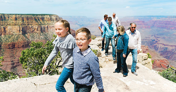 A family explores a canyon viewpoint with children in the foreground.