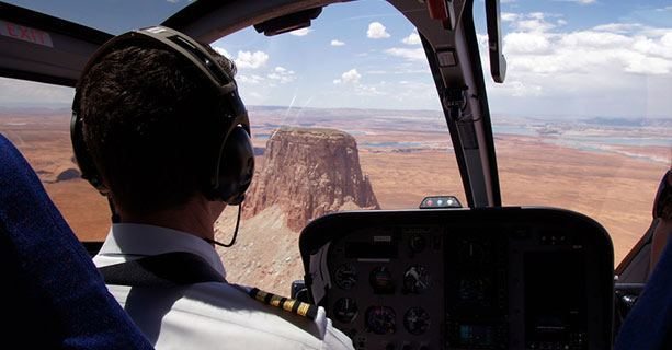A helicopter pilot navigates toward the top of Tower Butte.