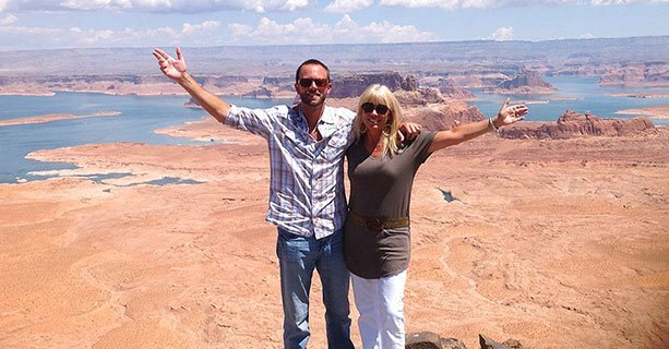 Two helicopter tour passengers standing atop Tower Butte with Lake Powell in the background.