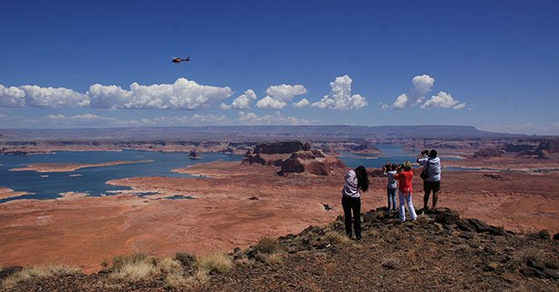 Passengers stand at the edge of Tower Butte as a helicopter soars by.
