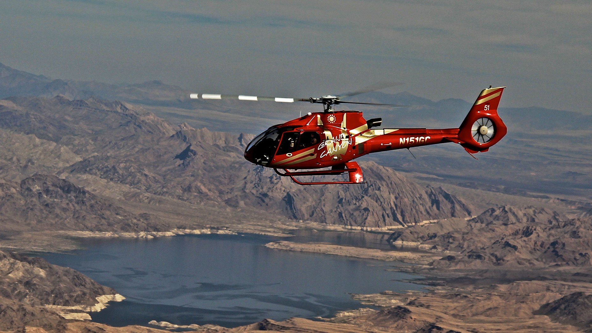 A red helicopter flies over the Mojave Desert and Lake Mead.