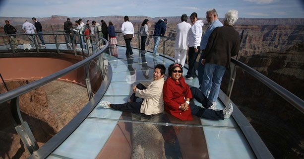 Two women sit on the glass floor of the Skywalk Bridge over the Grand Canyon.'