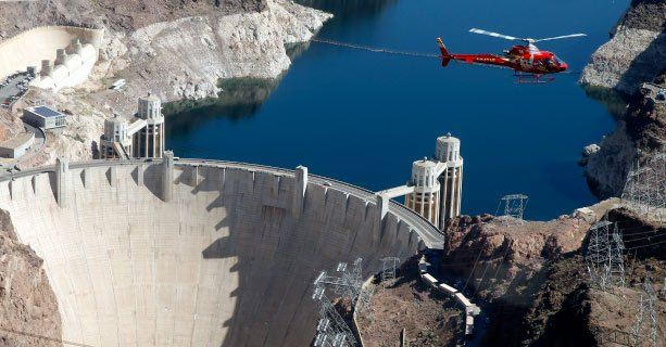 A helicopter en route to the Grand Canyon passes by the Hoover Dam.