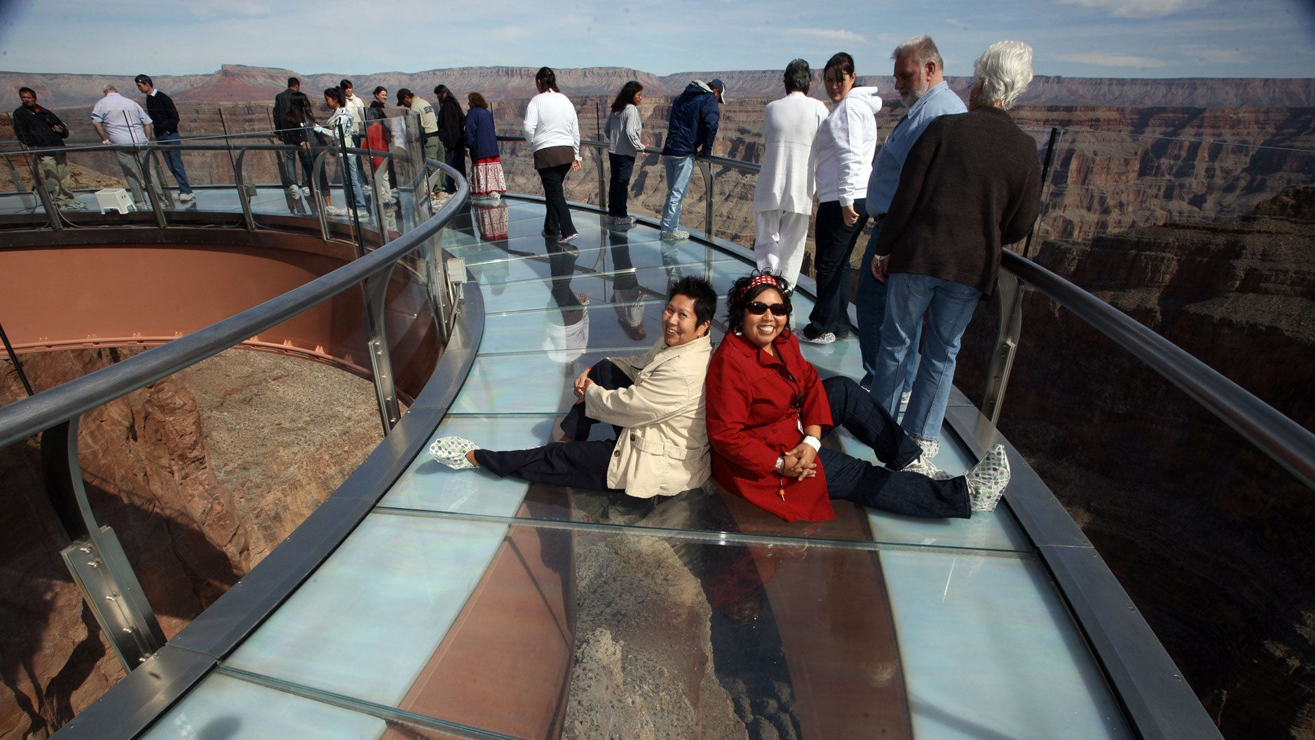 Two women sitting on the glass floor of the Skywalk posing for a photo. Tour departing from Boulder City