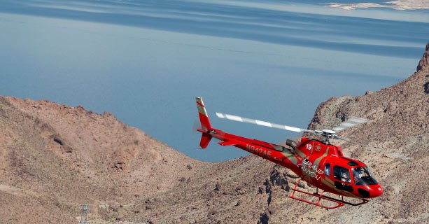 A Bell helicopter hovering over a crystal clear Lake Mead.