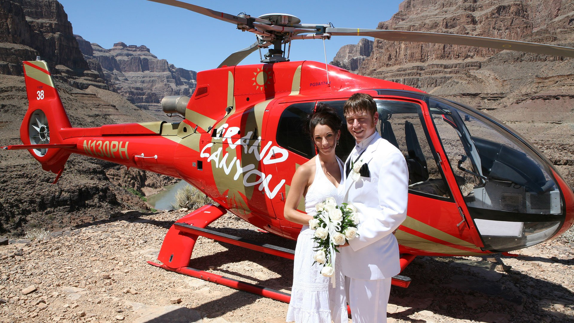 A bride and groom pose in front of a helicopter at the bottom of the Grand Canyon.