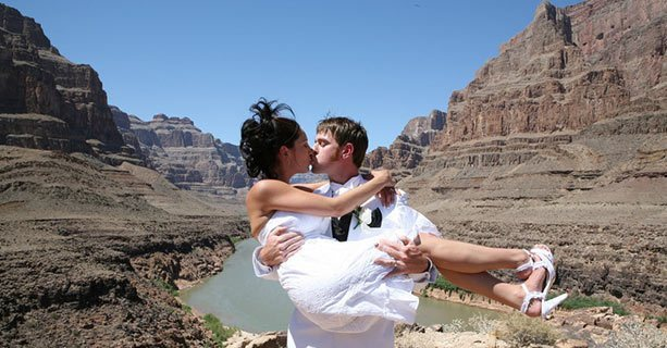 A newly-married couple kiss at the bottom of the Grand Canyon.