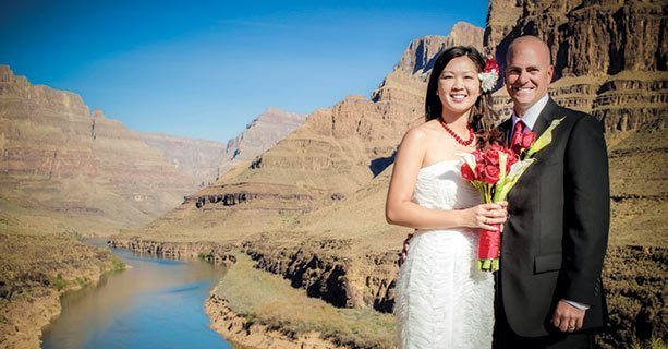 A bride and groom standing together on the canyon floor.'