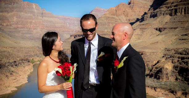 Newlyweds share a laugh with their minister at the bottom of the Grand Canyon.