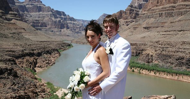 Bride and groom stand in front of the Colorado River on canyon floor.