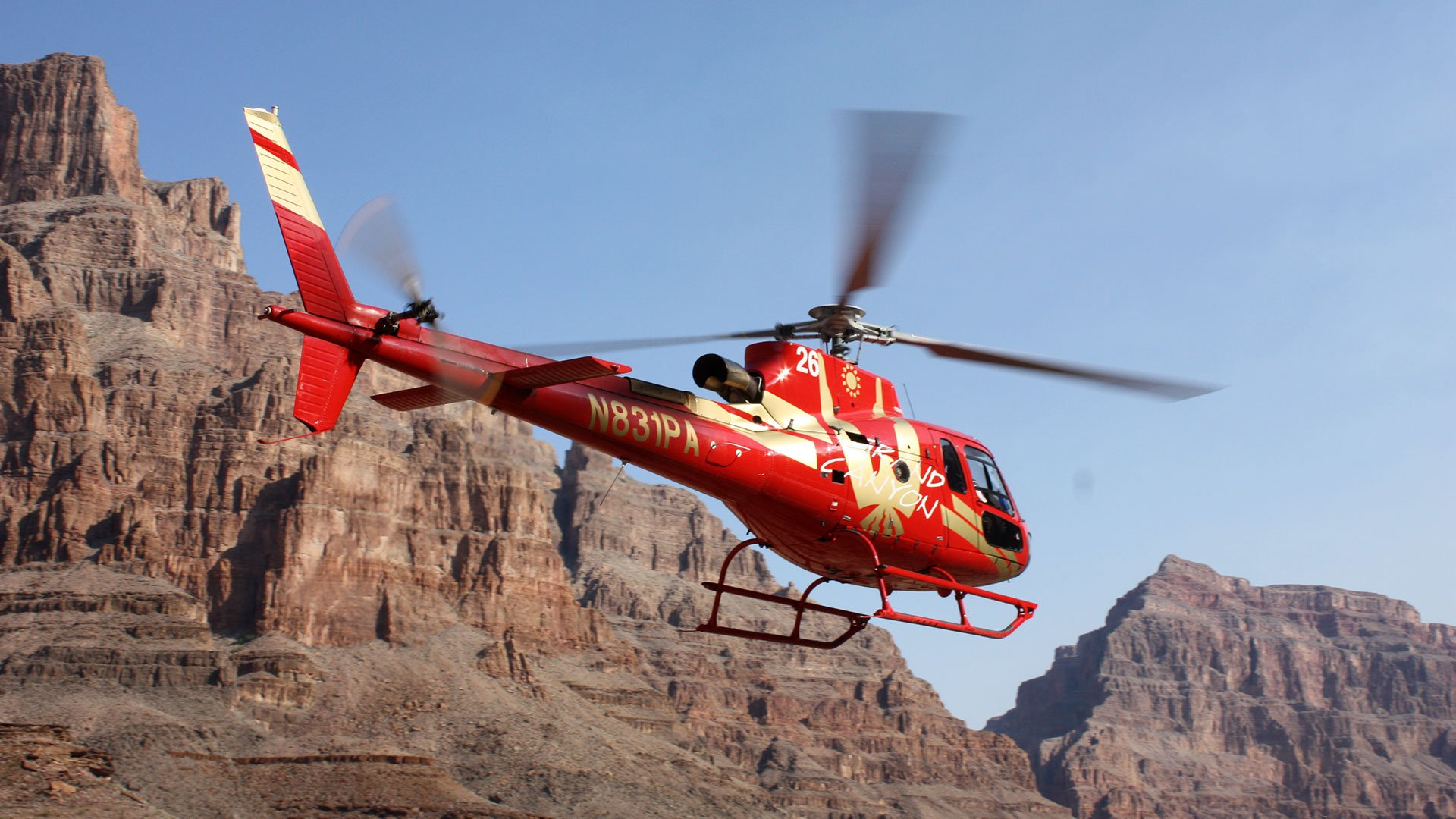 A red helicopter flies through the Grand Canyon West.