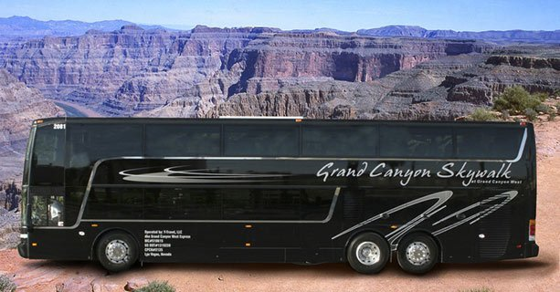 A black motorcoach parked with Grand Canyon scenery in the background.