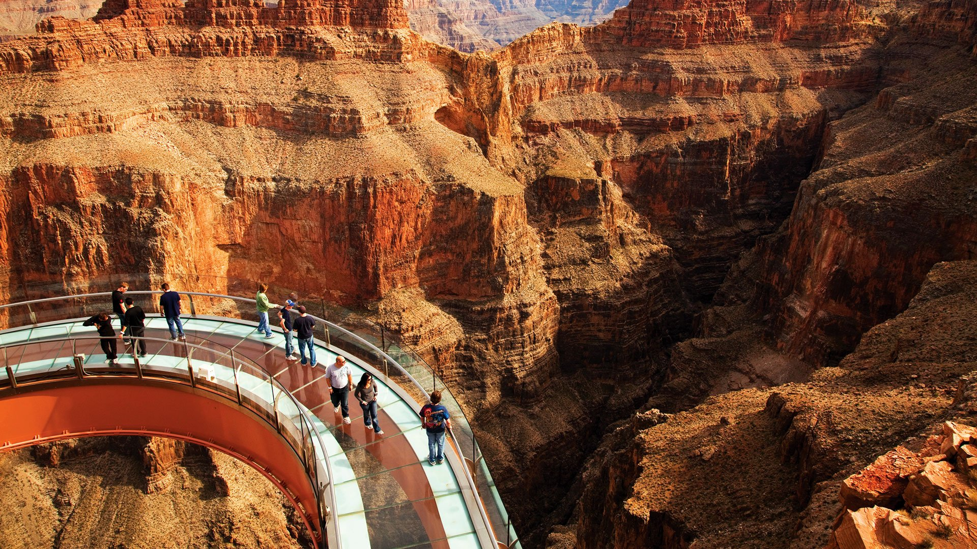 Guests walking on the Skywalk glass bridge with the Grand Canyon in the background.