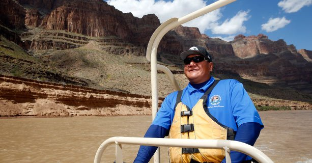 A man steering a pontoon boat along the Colorado River with the Grand Canyon behind him.