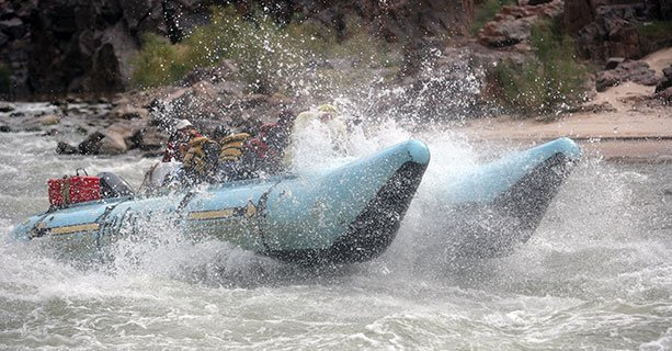 A raft splashes through some Colorado River rapids.