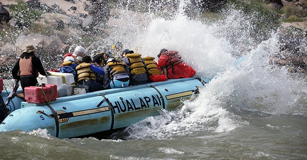 Passengers aboard a raft race through the rushing waters of the Colorado River.