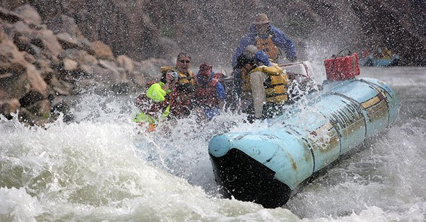 Passengers laugh aboard a rafting tour splashing through the Colorado River.