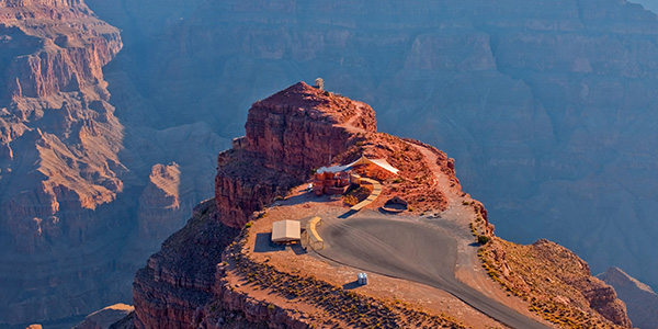 A paved drive, a building, and a tent sitting atop a Grand Canyon cliff formation. Tour departing from our Boulder City terminal.