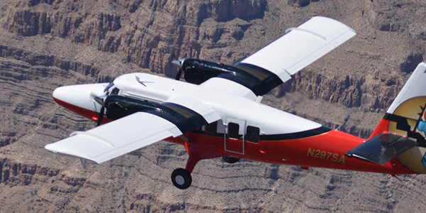 A red and white airplane flies over the Grand Canyon. Tour departing from our South Rim Terminal