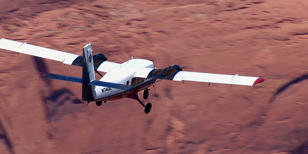 A Twin Otter airplane flies over the desert. Flight departing our Page, AZ terminal